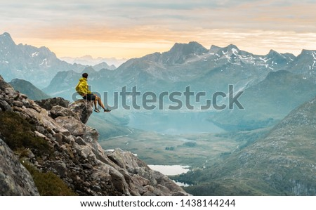 Hiking in the incredible jurassic wild landscape of green mountains, among glaciers and volcanoes. Adventurous man is on top of the mountain and enjoying the beautiful view during a vibrant sunset