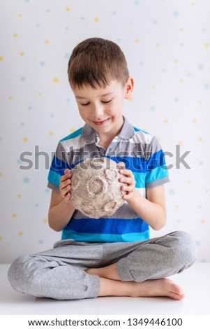 Сhild holds the moon in its hands with craters on a white starry background. A six year boy enthusiastically studies the mockup of a papier-mâché moon. Cosmonautics Day. Pre-school science education. Foto d'archivio ©