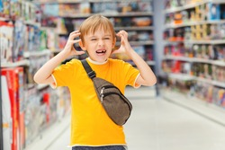?hildren's tantrum in the store. Boy can't selecting toy in kids store. Many toys around. Shop toys.Inside toy shop. Little boy getting hysterical in toy shop.Kid makes difficult choice in supermarke