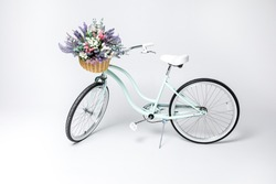 Hipster bicycle with basket full of fresh flowers  isolated on white