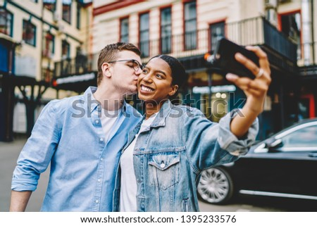 hipster guy kissing happy african american girlfriend which holding smartphone and making common selfie during trip in urban setting.Positive diverse marriage taking photo on mobile phone #1395233576