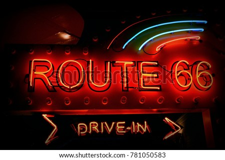 Historic Route 66. It is a neon sign in red against a black night sky.