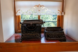 historical typewriter standing in front of the window
