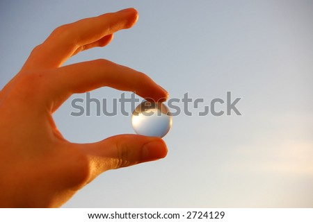 holding glass marble over blue sky