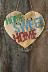 'Home Sweet Home' message wooden heart sign from recycled old palette on rough grey wooden background, copy space