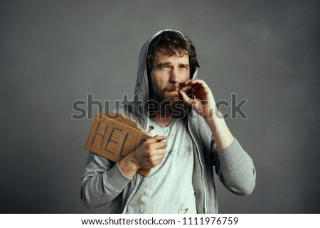 Stock Photo  Homeless man in dirty clothes smokes on a gray background