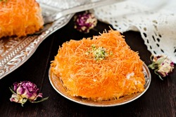 Homemade arabian traditional sweets Kunafa with pistachio and honey syrup on dark wooden background