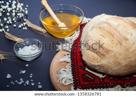 Homemade bread on a napkin embroidered in a hand cloth, near a transparent stick with salt, wheat ears, a dark background.   #1358326781
