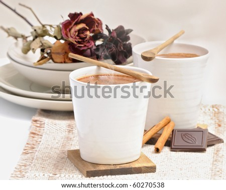 Hot Chocolate in white cups with Chocolate bar and cinnamon