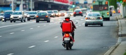 24 hours delivery service from cafes and restaurants. Takeaway, delivery boy on scooter with red isothermal backpack driving fast. Courier delivering food on motorbike to avoid evening traffic jams