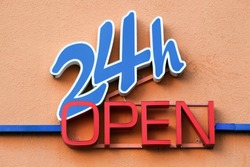 24 hours open sign on a wall