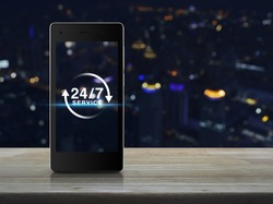 24 hours service icon on modern smart phone screen on wooden table over blur light city tower background, Full time service concept
