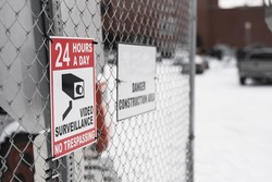 24 hours surveillance sign, warning people no trespassing on construction site.