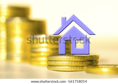 House on a background of columns of coins . The concept of financial instability in the market .
