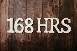 168 HRS Number of hours in a week with space copy on wooden background