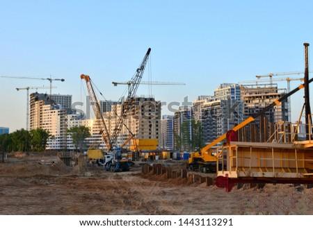 Huge construction site with a lot of construction equipment, houses under construction, tower cranes and workers. Piles driven into the ground by hydraulic hammering. Subway construction project