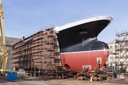 Hull of big ship under construction at shipyard.