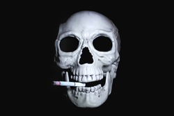 Human skull with a smoking cigarette in his mouth looking out of the dark