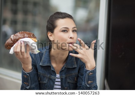 hungry girl eating a donut with chocolate and sucking her finger