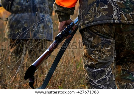 Hunter in camouflage clothes  with hunting rifle. Hunting in the forest