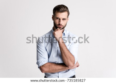 I have some doubt. Handsome young man looking at camera and keeping hand on chin while standing against white background.