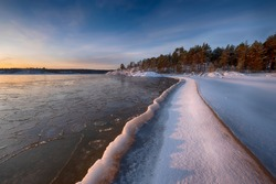 ice  coast on the water in Lake Ladoga at dawn with fresh snow in winter