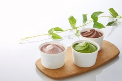 Ice cream in paper white cup, strawberry, green tea, and chocolate  flavours.