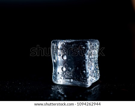 Ice cube on a black background is melting with drops of water. #1094262944
