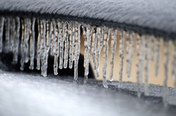 Icicles cover a car spoiler during an ice storm.