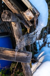 Icicles on the roof of a hay barn. Ice and snow in winter. Wood shovel at the edge of the forest. boarded, weathered wooden wall. simple hut in Vorarlberg, Austria. snow is sliding down from the roof