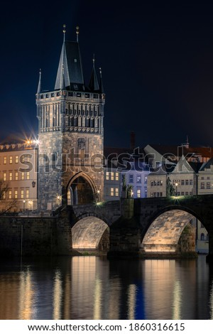 illuminated Charles Bridge from 14 centuries and light from street lighting and stone sculptures on the bridge and light reflections on the surface of the Vltava river at night in Prague