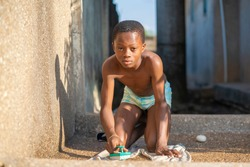 image of African boy with brush, on wet cloth-local laundry concept