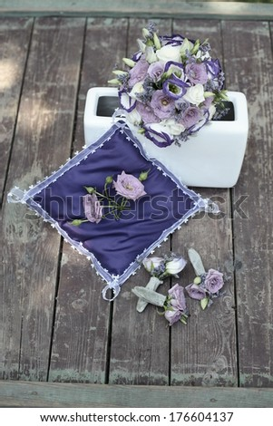 image of Purple and white wedding bouquet in a vase on a wooden base along with a decorative pillow