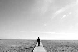 Imagen en blanco y negro en la que se ve a un hombre caminando por una pasarela de madera sobre la arena de una playa gigantesca