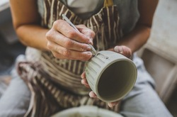 In the image female hands trace a striped pattern to a clay mug. For this a special tool is used. Image with a selective focus.