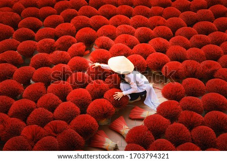 Incense sticks drying outdoor with Vietnamese woman wearing conical hat in Hanoi, Vietnam