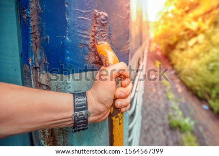 India, Maharashtra prospective image of Indian train with american tourist which hold a handle at sunset. Train to GOA. overpopulation concept