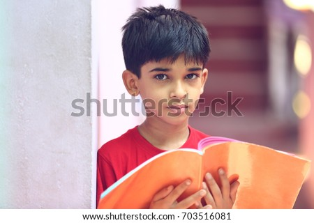 Free photos Portrait of cheerful elementary school student reading ... 1f4e0699a21ed