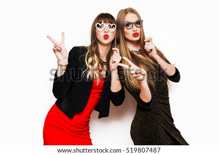 Indoor  lifestyle portrait of two bed friends, elegant women in evening dress Holiday makeup and bright party accessories posing on white wall, enjoying birthday or new year party.