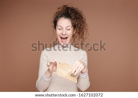 Indoor portrait of overjoyed young lady holds craft paper envelop, receives letter or postcard from friend, has good news, stares inside with blue eyes full of happiness. Human emotions concept.