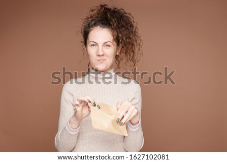 Indoor portrait of overjoyed young lady holds craft paper envelop, receives letter or postcard from friend, has good news, stares at camera with blue eyes full of happiness. Human emotions concept.