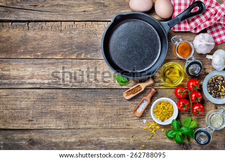 Ingredients for cooking and cast iron skillet on an old wooden table. Food background concept with copyspace