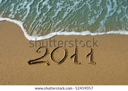 2011 inscription on the sand near the azure sea