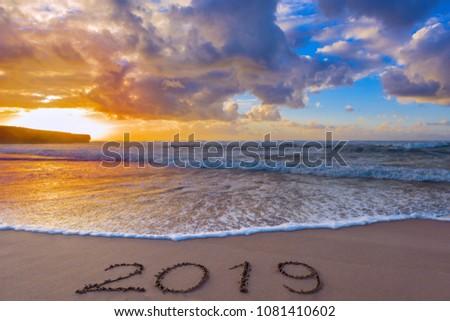 2019 inscription on wet beach sand and a dramatic sky.