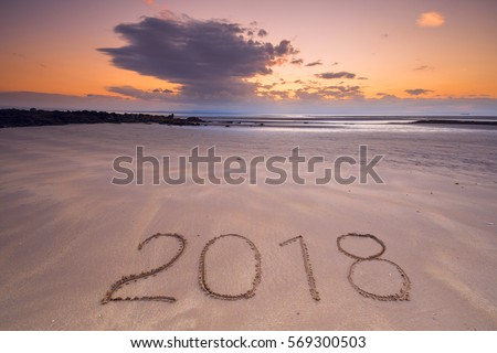 2018 inscription on wet sandy beach after ebb. Concept of celebrating the New Year. #569300503