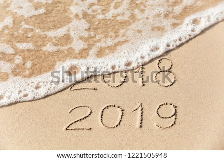 2018 2019 inscription written in the wet yellow beach sand being washed with sea water wave. Concept of celebrating the New Year at some exotic place #1221505948