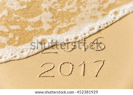 2016 2017  inscription written in the wet yellow beach sand being washed with sea water wave. Concept of celebrating the New Year at some exotic place #452381929