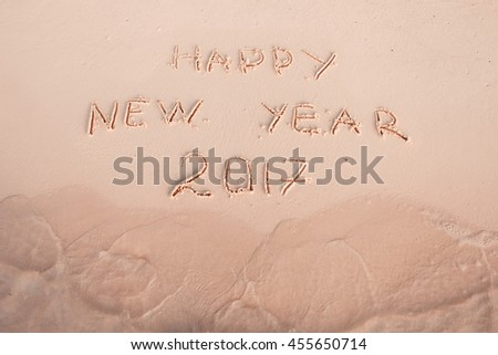 2016 2017 inscription written in the wet yellow beach sand being washed with sea water wave. Concept of celebrating the New Year at some exotic place #455650714
