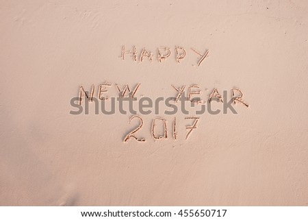 2016 2017 inscription written in the wet yellow beach sand being washed with sea water wave. Concept of celebrating the New Year at some exotic place #455650717