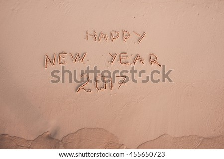 2016 2017 inscription written in the wet yellow beach sand being washed with sea water wave. Concept of celebrating the New Year at some exotic place #455650723